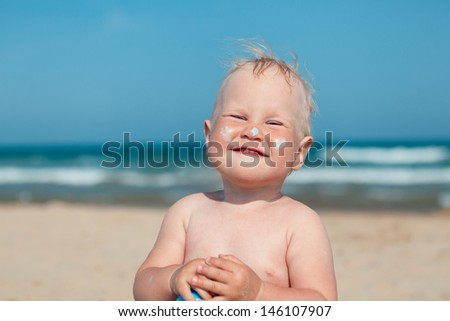 Adorable  small girl at beach applying sunblock cream - stock photo