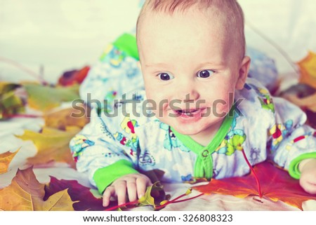 Adorable smiling baby boy with autumn multicolored maple leaves. Studio portrait. Image with vintage filter - stock photo