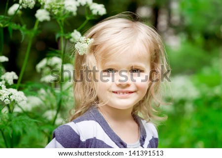 Adorable smiling blond little girl with flower in her hair in summer day - stock photo