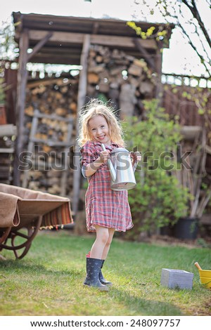 adorable smiling child girl in plaid dress helps in garden with watering can in sunny spring day - stock photo