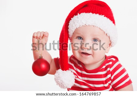 Adorable smiling child wearing red Christmas cap holding red christmas ball isolated on white - stock photo