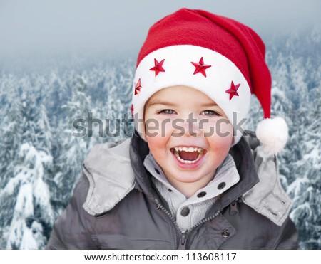 Adorable smiling child wearing Santa Claus christmas hat - stock photo