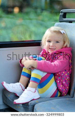 Adorable smiling girl riding bus sitting comfortable on passenger seat nearby the window. Portrait of smiling child on bus seat. Independent little kid travelling in urban environment. - stock photo