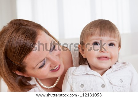 Adorable smiling little blonde girl with her doting mother posing for the camera - stock photo