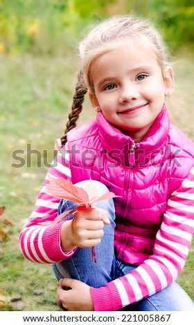 Adorable smiling little girl sitting on grass outdoor - stock photo