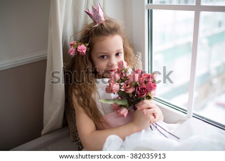 Adorable smiling little girl with  bouquet of flowers by the window - stock photo