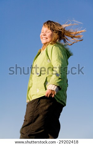 Adorable smiling little girl with hair flying over blue sky - stock photo