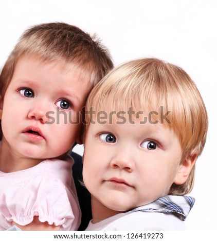 Adorable Smiling young happy brother kid and beauty sister baby, both wearing white, in a hug. Isolated on a white background in studio - stock photo