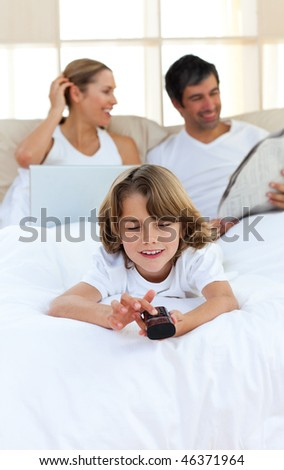 Adorable son watching TV in his parents bedroom - stock photo