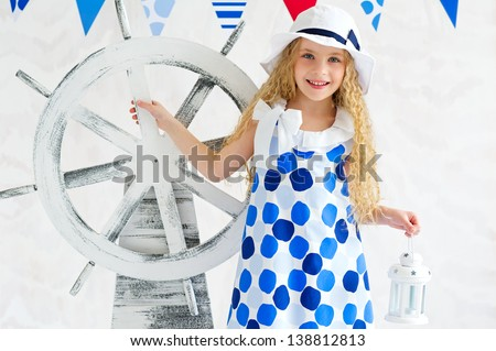 Adorable summer girl in spotted dress and fashion hat standing next to decorative steer wheel - stock photo