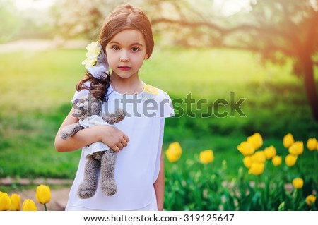 adorable surprised child girl with teddy bear on the walk in spring park with blooming tulips on background - stock photo