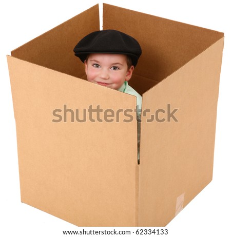 Adorable three year old boy with hat in a cardboard box over white background. - stock photo