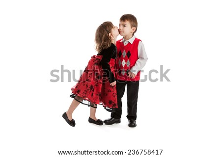 Adorable three year old fraternal brother and sister twins in Christmas outfits kissing isolated on a white background - stock photo