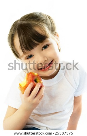 adorable three year old girl eating an apple and smiling - stock photo