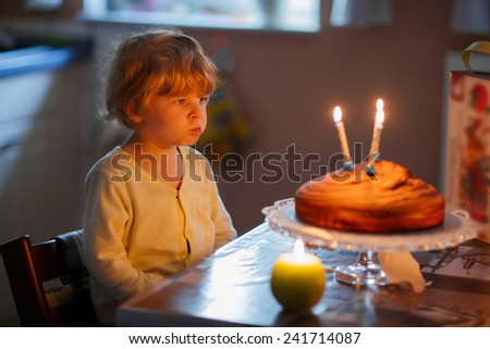 Adorable three year old kid boy celebrating his birthday and blowing candles on his cake in domestic kitchen. - stock photo