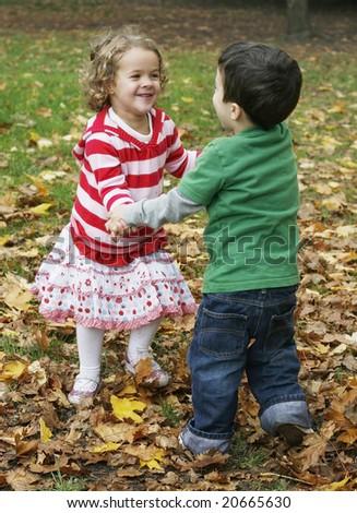 adorable toddler boy and girl dancing - stock photo