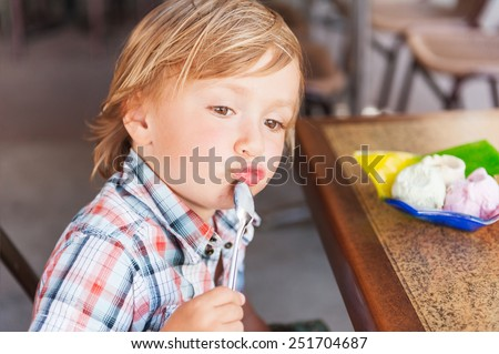 Adorable toddler boy eating ice cream in a cafe on a very hot day - stock photo