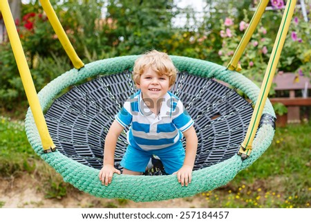 Adorable toddler boy having fun chain swing on outdoor playground. child swinging on warm sunny summer day. Active leisure with kids. - stock photo