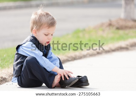adorable toddler boy in suit trying to put his shoes on - stock photo