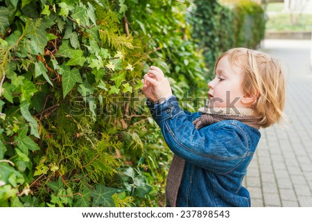Adorable toddler boy playing with plants outdoors on a fresh spring day - stock photo