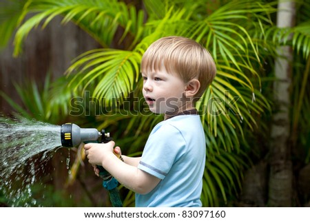 Adorable toddler boy watering plants in the garden - stock photo