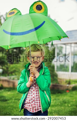 Adorable toddler boy with green frog umbrella. Outdoors portrait - stock photo