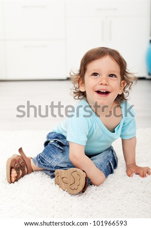 Adorable toddler child laughing on the floor - happy childhood concept - stock photo