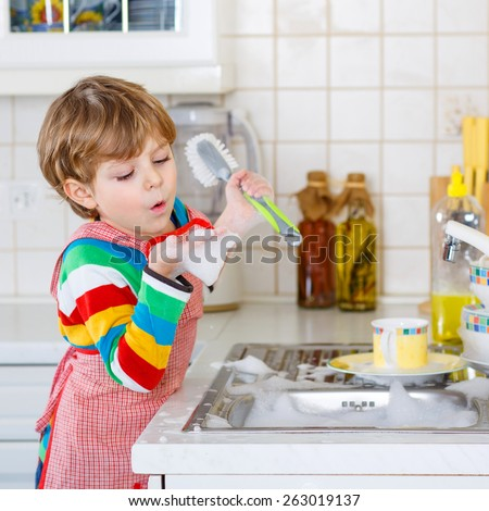 Adorable toddler child washing dishes in domestic kitchen. Little boy having fun with helping his parents with housework. Indoors, kid in colorful clothes. - stock photo
