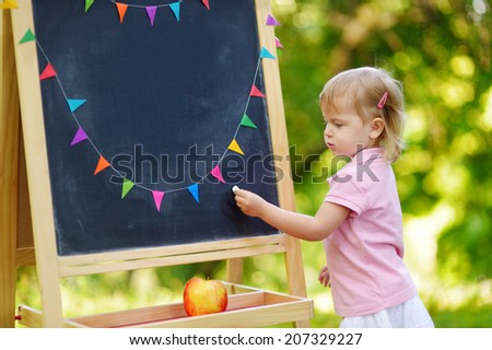 Adorable toddler drawing with a chalk on a blackboard - stock photo