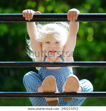 Adorable toddler girl acting like a monkey outdoors at summer - stock photo