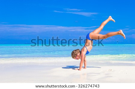 Adorable toddler girl have fun at beach during summer vacation - stock photo