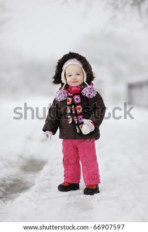 Adorable toddler girl having fun at  beautiful winter day - stock photo