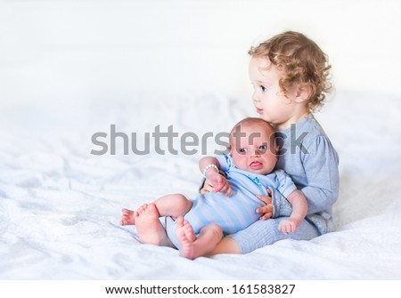 Adorable toddler girl holding her newborn baby brother - stock photo