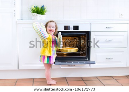 Adorable toddler girl in a yellow dress wearing colorful mittens playing in the kitchen next to a modern white oven helping by cooking and baking an apple pie in a home with white interior - stock photo