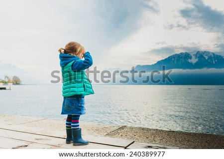 Adorable toddler girl playing by the lake, looking at the mountains, wearing, rain boots, jeans skirt and green waistcoat - stock photo