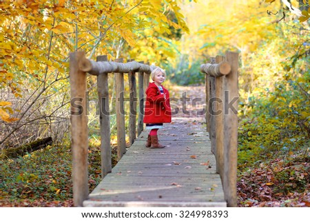 Adorable toddler girl playing in beautiful autumn forest. - stock photo