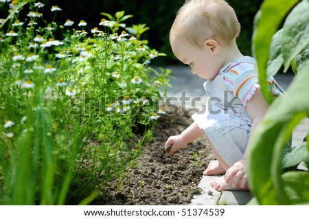 Adorable toddler girl playing in the garden - stock photo