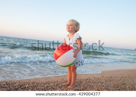 Adorable toddler girl playing with ball on white sand beach - stock photo
