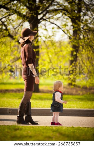 Adorable toddler girl walking with her Mom in the park. Summer. Warm colorful natural light. Last things in hat. Thrifty apple-trees - stock photo