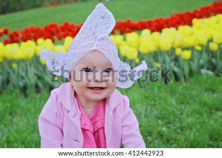 Adorable toddler girl wearing Dutch traditional national costume hat playing in a field of blooming tulips in Amsterdam region, Holland, Netherlands. Happy child against spring flowers background - stock photo