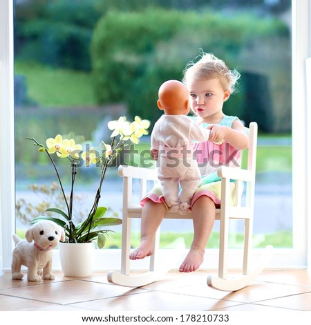 Adorable toddler girl with blond curly hair playing indoors with doll sitting on a rocking chair in white sunny room with big street view window - stock photo