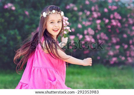 Adorable toddler little girl having fun outdoors and dancing, swirling around, holding roses, wearing pink dress - stock photo
