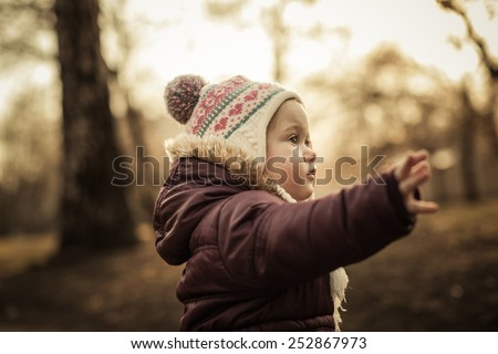 Adorable toddler running forward in the park. Cold spring. Warm colors. - stock photo