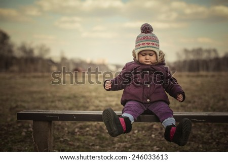 Adorable toddler serious girl sitting on the branch. Cold Autumn. Background field, clouds, trees. Funny boots on her feet - stock photo