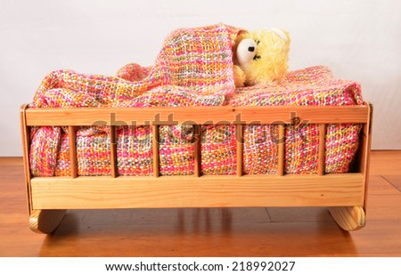 Adorable toy covered with a blanket in a crib. - stock photo