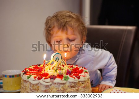 Adorable two years old toddler kid celebrating his birthday and blowing candles on homemade baked cake, indoor. Birthday party for kids. Focus on cake - stock photo