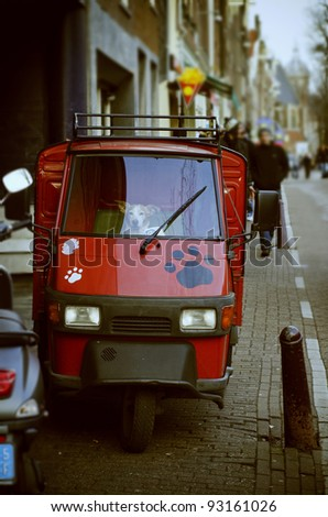 Adorable white dog sitting behind steering of a small italian truck - stock photo