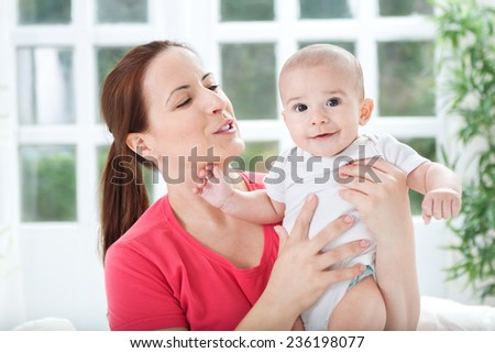 Adorable woman playing and smiling with her baby - stock photo