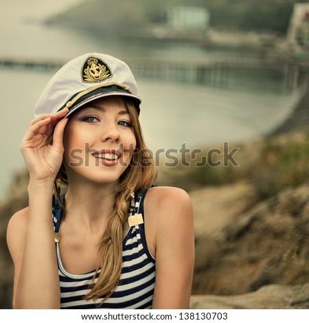 Adorable woman wearing sea Captain's cap and sexy sailor T-shirt - stock photo