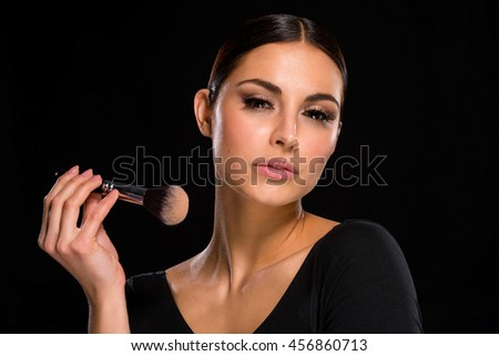 Adorable woman with brush in her hand for putting on base on the skin. Accurate variant for everyday make-up. Brunette looks right in the camera. - stock photo